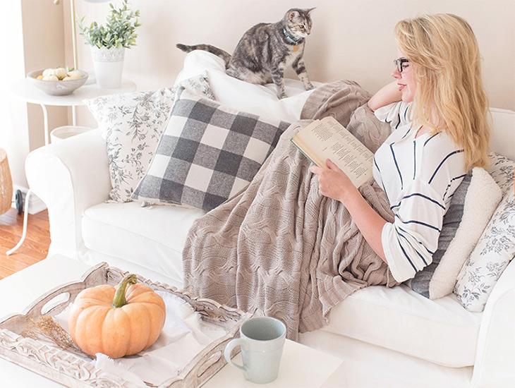 Exemple de parfaite fangirl de lecture : une femme qui lit allongée sur un divan avec un plaid, son chat et une tasse près d'elle