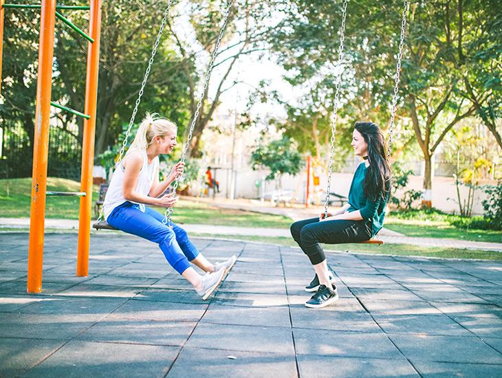 Comment se lier d'amitié avec un ou une accro de la lecture ? — Image de deux jeunes femmes assises face à face sur des balançoires en train de discuter et de sourire