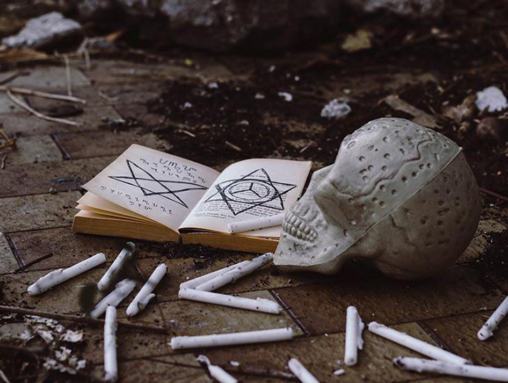 Pourquoi les livres d'horreur sont-ils bien plus flippants ? — Image d'un livre ouvert avec des inscriptions étranges. Le livre est posé sur un sol sali de terre près d'un crâne de squelette et de bougies éteintes.
