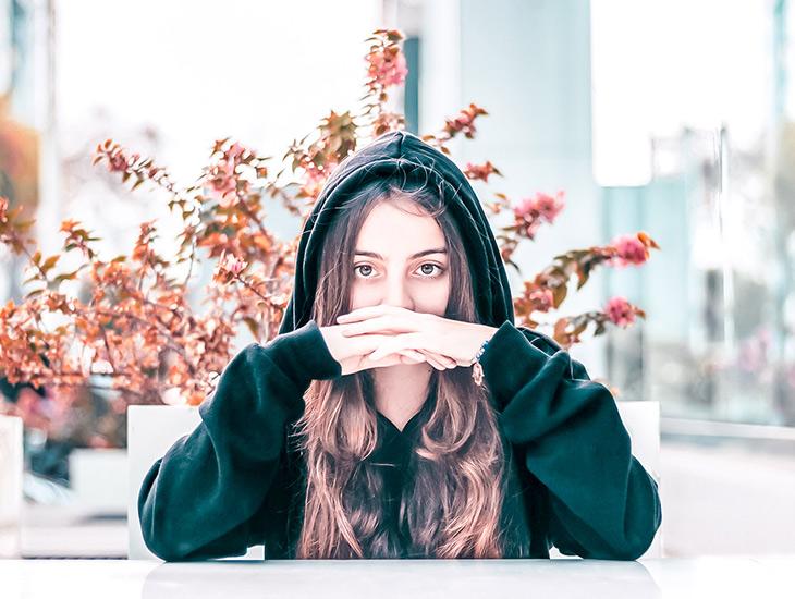 6 choses que les personnages de fictions font et qu'on ne pige pas — Image d'une jeune femme ayant les mains jointes devant le visage et l'air songeur, se demandant pourquoi les personnages font-ils cela